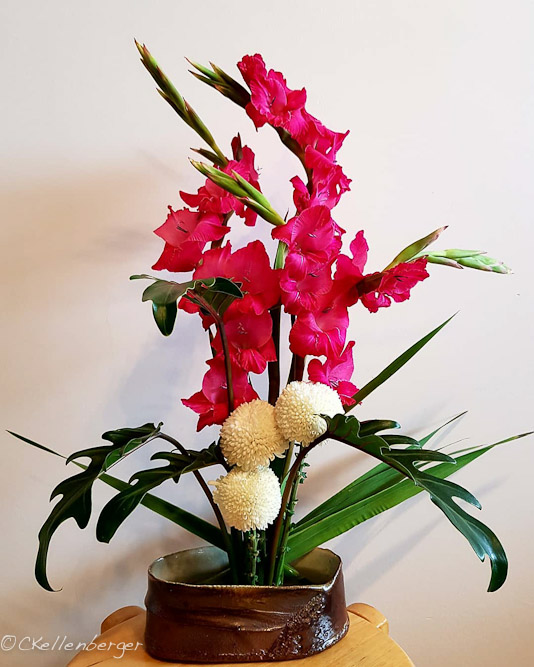 Ikebana arrangement: Hot pink Gladiolus, lily leaves, white chrysanthemums