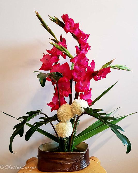 Ikebana arrangement: Hot pink Gladiolus, lily leaves, white chrysanthemums